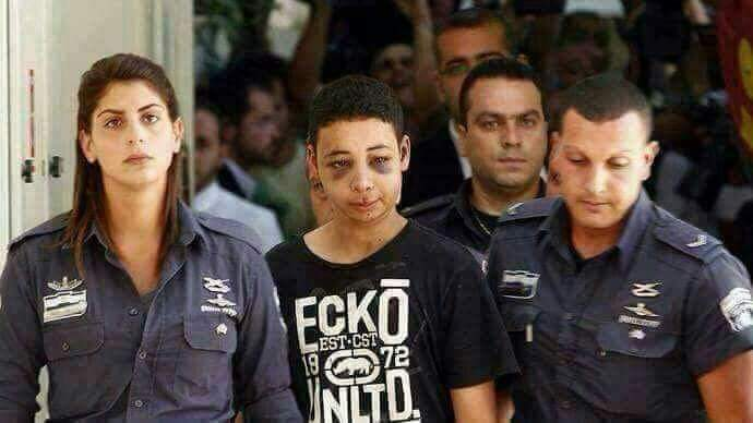 Photo of Palestinian child with bruised face being taken by Israeli police officers