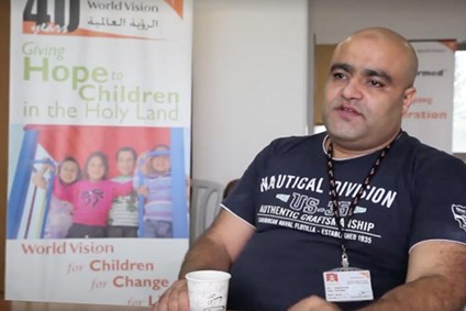 Picture of Mohammed El Halabi with World Vision baner behind him