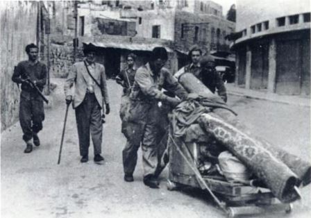 Historical photo of people pushing belonings on a trolley