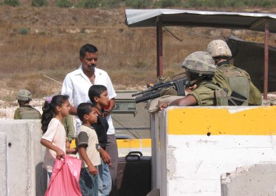 Photo of Palestinian children at a checkpoint with a solider with a gun pointed at them