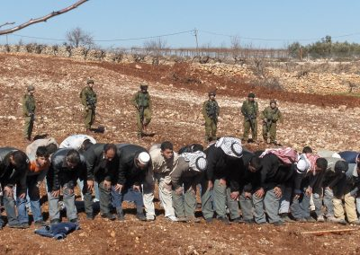 Photo of men praying in dry field with Israeli soldiers